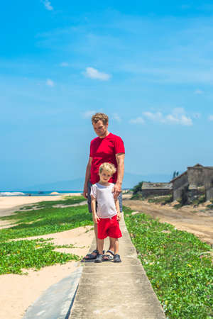 Father son walk along narrow concrete path, sea blue clear sky green grass background. Symbol as dad leads child into future adulthood. Happy childhood, fathers day, daddy influence on boy worldview