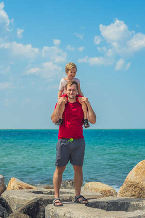Happy smile father hugs holds on shoulders boy male child stand blue lazur sea panorama skyline horizon sunshine day clear sky. Travel, relationship, dad responsibilities, influence on son worldview Stock Photo