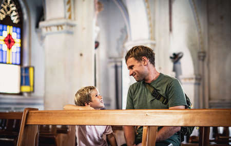Christian dad tells his son Bible stories about Jesus sitting in kirk. Faith, religious education, modern church, father day, fatherly responsibilities, father influence on formation of son worldview