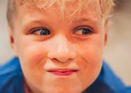 Close up portrait cute smiling blue eyed freckled blond boy pronounced artistic facial expressions, gestures, intriguing cunning funny mischievous. Happy childhood, children behaviour problems concept