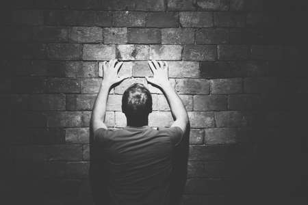 Rear view man under life crisis problems stand facing looking brick wall, hands raised up on wall take sign, wants to climb, overcome obstacle, reach a goal, leader, motivation. Black white toned