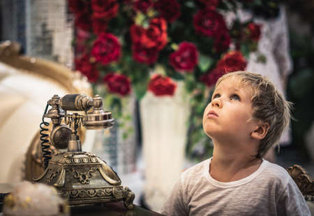Boy look up, play with antique vintage rotary old hang up telephone beautifully embossed gold bronze texture retro style. Old landline phone. Concept of wealth, prosperity, beauty of last century art