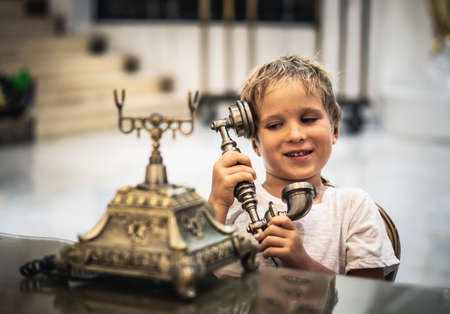 Boy take telephone receiver, play with antique vintage rotary old landline hang up phone beautifully embossed gold bronze texture retro style. Concept of wealth, prosperity, beauty of last century art
