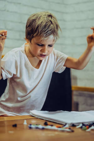 Portrait blond cute Preschool boy raised hands waving angry that fails work learn write draw notebook, expressive facial emotions gestures. Children behaviour education problems, home school concept