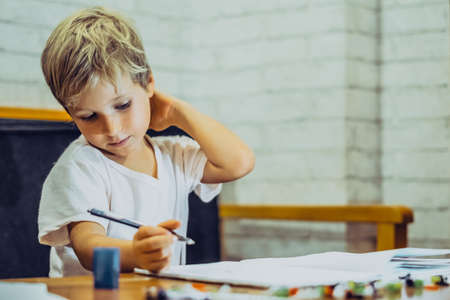 Portrait Preschool boy thoughtfully scratches back neck with hand, learn write draw holding pen notebook, emotion facial expressions gestures. Children behavior education problems, home school concept 版權商用圖片