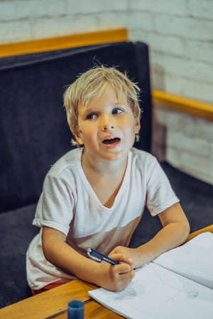 Preschool boy mischievous dreamy intriguing funny look, open mouth, thoughtful hold pen notebook, think idea draw doodle, facial expressions gestures. Home education, develop imagination concept