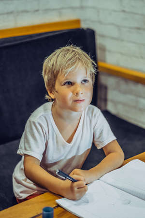 Portrait Preschool boy dreamy airy fairy look up thoughtful, hold pen notebook, think idea to draw write, facial expressions gestures. Children education, home school, develop imagination concept