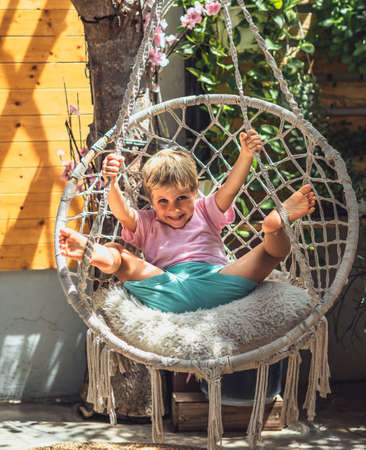 Cute smile blond boy happy mood childhood joys emotion facial expression gestures mischievous in pink, sun beams yard, sit swing Hammock Chair Hanging. Funny photo, happiness children behaviour Archivio Fotografico