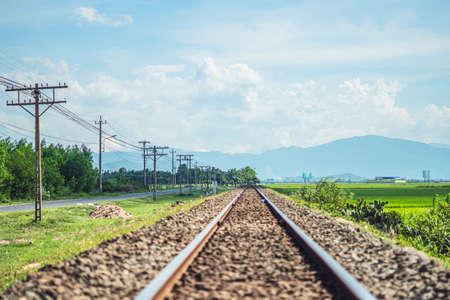 Railway tracks line forward gravel, horizon beauty cloudy blue sky, electric poles, landscape sun mountain background. Railroad travel tourism, transportation industrial concept summer day Imagens