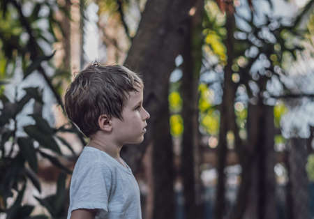 Side view kid child six year boy looking straight serious sad in white t-shirt outside nature background. Dark mood, childhood parenthood psychology education problems crisis due COVID concept