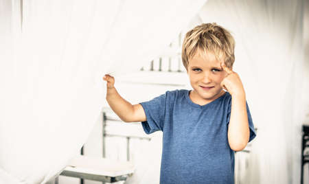 Portrait sly smile narrowed eyes freckled boy points finger to head have idea, facial expression hand gesture. Funny mischievous mood. Happy childhood, behaviour education psychology relationship