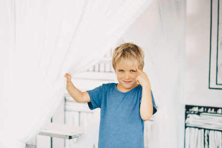 Portrait sly smile narrowed eyes freckled boy points finger to head have idea, facial expression hand gesture. Funny mischievous mood. Happy childhood, behaviour education psychology relationship Imagens