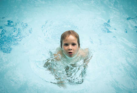 Innocence easy lifestyle collection. Time to stop worry even in crisis, follow the example of children. Wet kid swim in pool, dives sink in water, eyes look at camera, mouth open say. Childhood Imagens