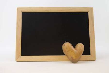 Heart shaped potato in front of a blackboard - copy space
