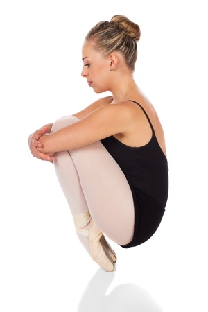 Beautiful young female classical ballet dancer on pointe shoes wearing a black leotard and pink stockings isolated on a white studio background photo