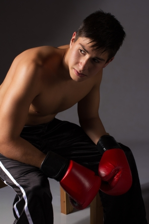 kickboxer: Young handsome male caucasian kickboxer wearing red boxing gloves and kickboxing gear isolated on a neutral background