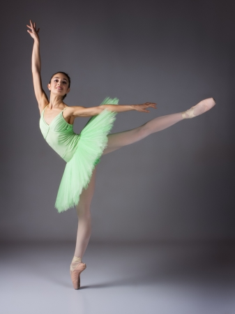 Beautiful female ballet dancer on a grey background. Ballerina is wearing a green tutu and pointe shoes. photo