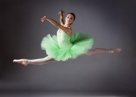 회색 배경에 아름 다운 여성 발레 댄서. 발레리나 녹색 스커트와 포인트 슈즈를 착용하고 있습니다.