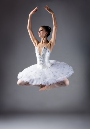 Beautiful female ballet dancer on a grey background. Ballerina is wearing a white tutu and pointe shoes. photo