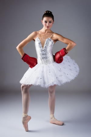 Beautiful female ballet dancer on a grey background  Ballerina is wearing a white tutu, pointe shoes and red boxing gloves  photo