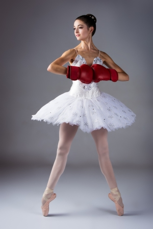 ballerina shoes: Beautiful female ballet dancer on a grey background  Ballerina is wearing a white tutu, pointe shoes and red boxing gloves  Stock Photo