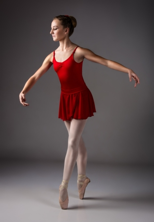 Beautiful female ballet dancer on a grey background  Ballerina is wearing a red leotard, pink stockings, pointe shoes and a red dress  photo