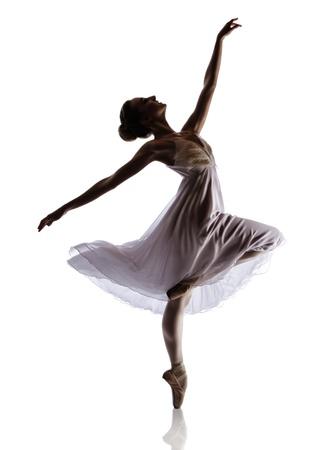 Silhouet van een mooie vrouwelijke balletdanser geïsoleerd op een witte achtergrond. Ballerina draagt een witte jurk met veren en pointe schoenen. Stockfoto