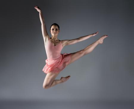 Mooie vrouwelijke balletdanser op een grijze achtergrond. Ballerina is blootsvoets en het dragen van een oranje jurk en maillot.