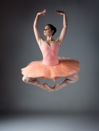 ballerina shoes: Beautiful female ballet dancer on a grey background. Ballerina is wearing an orange tutu, pink stockings and pointe shoes.