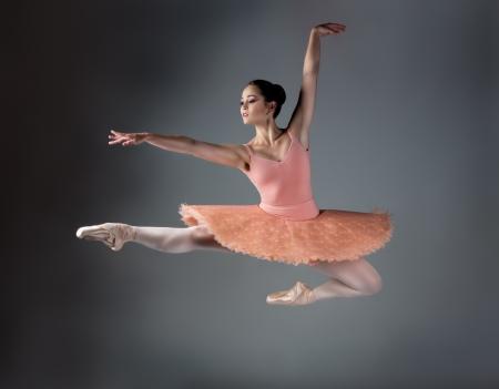 Mooie vrouwelijke balletdanser op een grijze achtergrond. Ballerina draagt een oranje tutu, roze kousen en pointe schoenen. Stockfoto