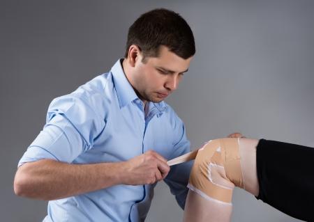 tendones: Macho adulto fisioterapeuta flejes de la rodilla de un paciente de sexo masculino