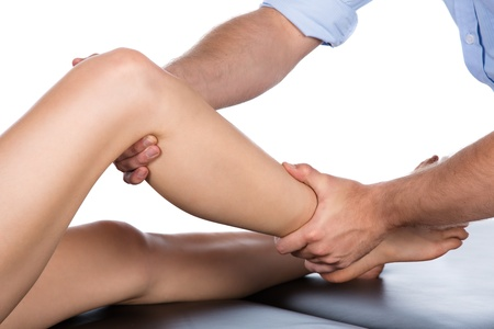 physiotherapist: Adult male physiotherapist treating the foot of a female patient  Patient is sitting on a bed