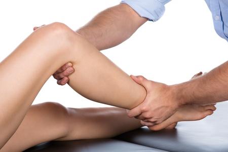 fisioterapia: Macho adulto fisioterapeuta tratar el pie de un paciente paciente est� sentado en una cama