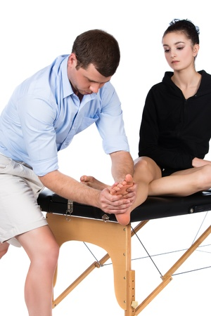 Adult male physiotherapist treating the foot of a female patient. Patient is sitting on a bed. photo