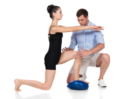 Adult male physiotherapist is assisting a female patient in rehabilitation exercises. photo