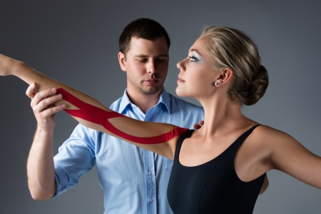 physiotherapist: Beautiful female ballet dancer and her physiotherapist on a grey background  Ballerina is wearing a black leotard and has red strapping on her arm