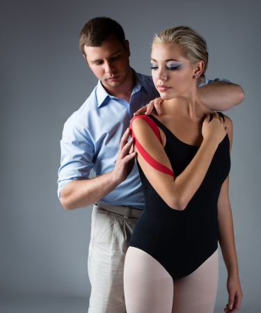 strapping: Beautiful female ballet dancer and her physiotherapist on a grey background  Ballerina is wearing a black leotard and has red strapping on her arm