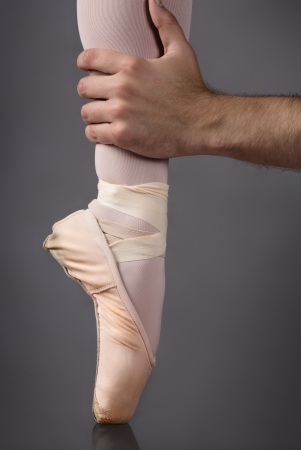 Male hand grasping the ankle of a female ballet dancers foot in a pink pointe shoe. photo