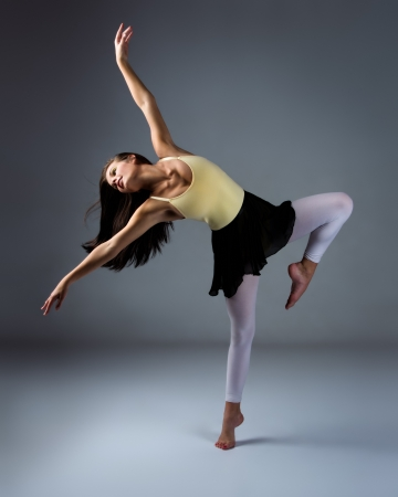 jazz dance: Beautiful female modern jazz contemporary style dancer on a grey background. Dancer is barefoot and wearing a yellow leotard, black skirt and pink stockings. Stock Photo