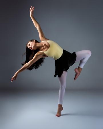 Mooie vrouwelijke moderne jazz eigentijdse stijl danser op een grijze achtergrond. Dancer is blootsvoets en gekleed in een geel maillot, zwart rokje en roze kousen. Stockfoto
