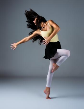 Mooie vrouwelijke moderne jazz eigentijdse stijl danser op een grijze achtergrond. Dancer is blootsvoets en gekleed in een geel maillot, zwarte rok en roze kousen.
