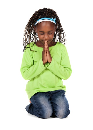 Adorable small african child with braids wearing a bright green shirt and blue jeans. The girl is kneeling and praying. photo