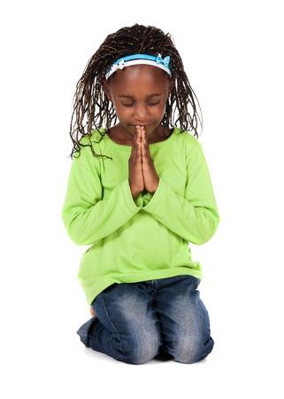 Schattig klein Afrikaans kind met vlechten dragen van een fel groen shirt en blauwe spijkerbroek. Het meisje is geknield en bidden.