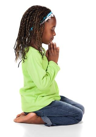niño orando: Adorable niño pequeño africano con trenzas llevaba una camisa verde y jeans azul brillante. La chica está de rodillas y rezando.