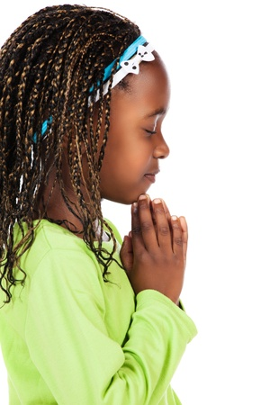 Adorable small african child with braids wearing a bright green shirt. The girl is kneeling and praying.
