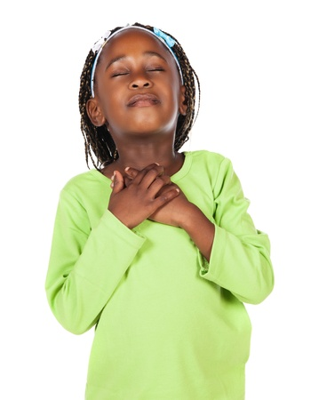 worship white: Adorable small african child with braids wearing a bright green shirt. The girl is praying with her hands on her heart. Stock Photo