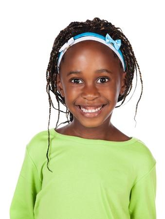 Schattig klein Afrikaans kind met vlechten draagt een fel groen shirt. Het meisje bevindt zich en lacht naar de camera.
