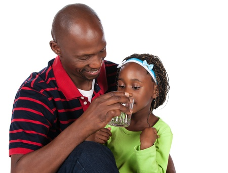 red water: Adorable small african child with braids wearing a bright green shirt and blue jeans is with her father. He is wearing a red striped shirt and is helping her to drink water from a glass.