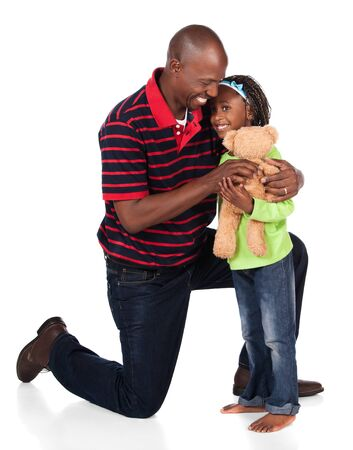 Adorable small african child with braids wearing a bright green shirt and blue jeans is playing with her father. He is wearing a red striped shirt and is giving her a teddy bear. photo