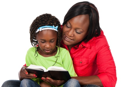 kid reading: Adorable small african child with braids wearing a bright green shirt and blue jeans and her mother wearing a red shirt. The mom is reading to the girl from a book.